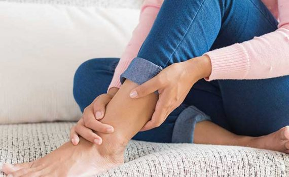 image of a woman holding her restless leg.